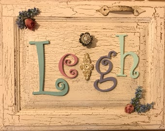 Name Plaque for Girl's Bedroom or nursery on old distressed wood with knobs and pulls, painted wooden letters, and flowers.