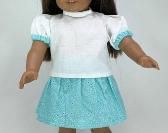 A complete 18 inch doll outfit including a white blouse, turquoise floral capris and skirt, and clear jelly shoes with turquoise bows.