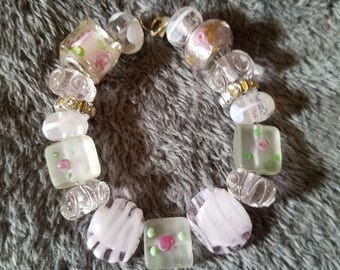 Precious tiny pink roses with green leaf accents adorn this beautiful bracelet