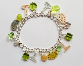 Green and silver charm bracelet with glass beads and shrink plastic charms