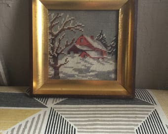Gold framed needlepoint log cabin