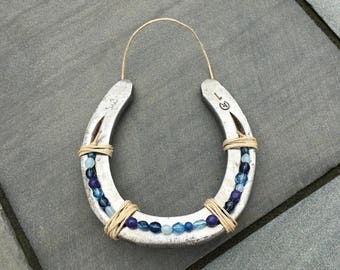 Beaded horseshoe hand-embellished with beads in various shades of blue and hemp