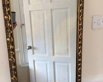 Large, very old and heavy gilt framed mirror.