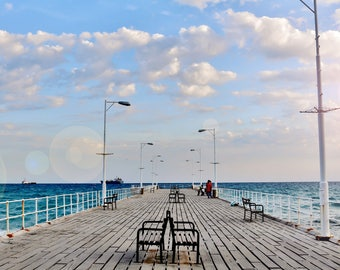 A long view of a wooden pier in a blue sea and under a blue sky with fluffy clouds.