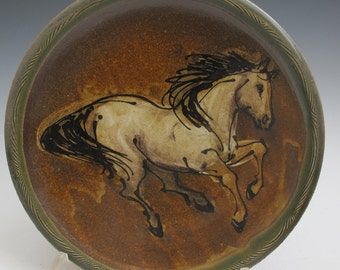 Horse painted and slip trailed on plate with  amber glaze