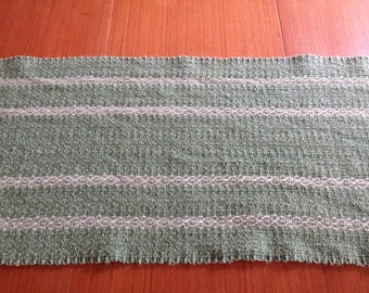 Handwoven table runner in sage green with natural patteen stripes