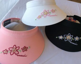 One Popular adjustable  4-inch adjustable visor with three plumerias embellished with Swarovski crystals! Pick your visor color!