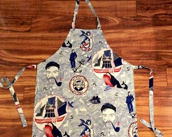 LOST AT SEA cream sailor style apron with sexy mermaid, dapper sea captain, and full sails ahead