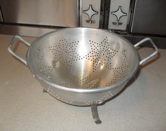 Vintage Aluminum Colander or Strainer with Star Shaped Perforations resting on 3 aluminum feet
