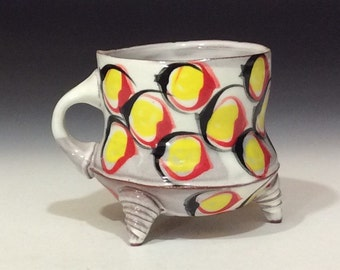 Yellow dots red and black circles on white footed mug.