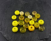 20 assorted yellow glass spacer beads.