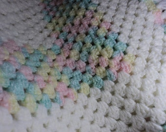 Baby throw in shades of white, yellow, pink, and mint green