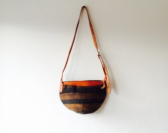 Woven sisal bucket boho bag with leather details.