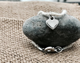 Tiny silver heart with white baseball leather inserted hung on real baseball string!