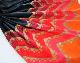 Black art silk fabric with shades of orange and red and gold foil print