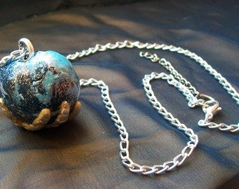 Gem globe-necklace hand supporting Earth-Earth polymer hand necklace. Jewel in the hand-Fee2mains world