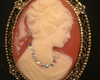 Cameo Oval Shaped Brooch with gold bronze filigree border and rhinestone necklace design