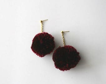 Pom-pom drop earrings dangling on gold chain and gold stud in burgundy