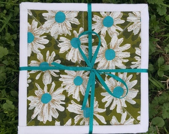 Mug Rugs Set of four (4) Quilted Coasters made of camo green fabric with a white and teal daisy print, finished like a mini quilt