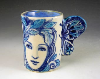 Butterfly winged porcelain cup with three women in turquoise, blue and white fresh out of the kiln