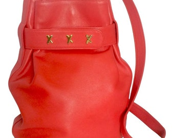 Vintage Paloma Picasso red leather hobo bucket style shoulder bag with golden logo motifs.