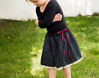 Girls twirly black polka dot skirt with pompom trim, ball fringe, tie waist, sizes 12 m to 12 years drawstring