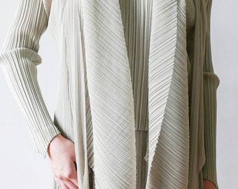 A three piece ensemble by ISSEY MIYAKE-PlEASE PLEATS-The set combines a jacket, blouse and skirt