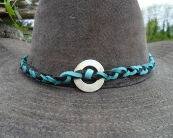 Tour(Tower,Ballot) of hat turquoise blue and black leather gives a pearly gloss to pearls and to feathers