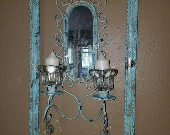 Antiqued mirror and candle holders in frame.