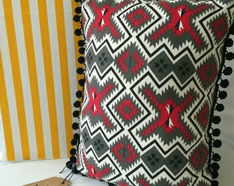 Red, black, and charcoal grey tribal pom pom pillow