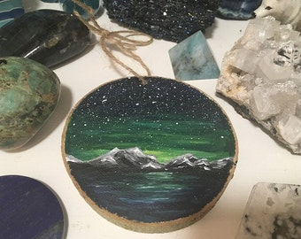 Hand painted wooden disk ornament - green mountain galaxy