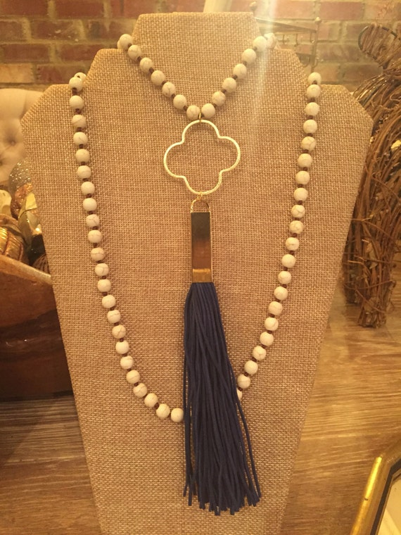 Double wrap knotted howlite with blue gold cap tassel. Gold clover hoop embellishment.