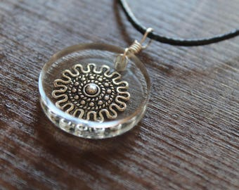 Necklace with round resin pendant containing a charm mandala