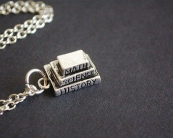 silver tone pile of books necklace