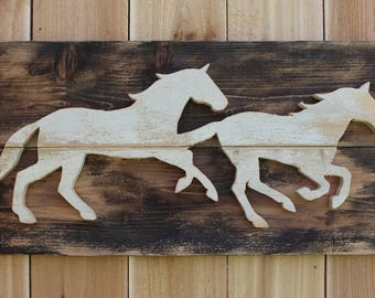 White running horses cutout on brown wood