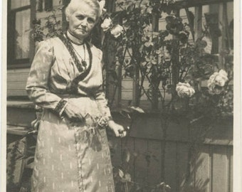vintage photo 1912 Older Woman Clips Rose Flower from Arbor by Home