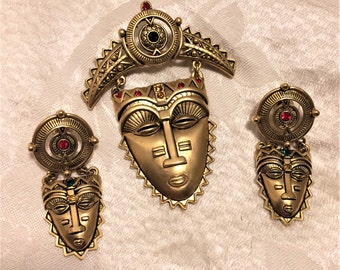 Vintage Avon Tribal Mask Dangle Brooch and Pierced Earring Set. Matte Goldtone Metal with Green and Red Rhinestones. Brooch Over 3 Inches D7