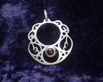 Saw pierced sterling silver domed pendant with garnet