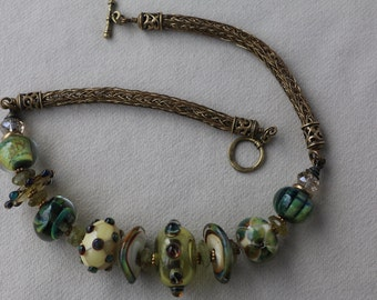 Lampwork, with a brass handmade viking knit necklace.