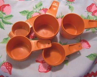 orange tupperware measuring cups