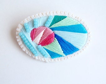 Hand embroidered brooch with colorful bursts of blues and pinks with light blue bead accent on cream muslin with cream felt backing