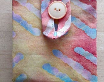 Fabric tea bag holder made of peach and gold batik fabric.