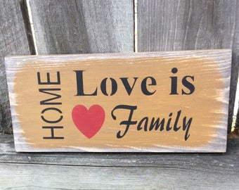 "Handmade wooden sign. ""Home* Love is Family"". Great addition to any home. Antiqued, stenciled, colors offered. Warm sentiment so fun."