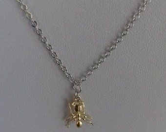 A modern tiny quirky matte gold plated ant charm pendant necklace on a fine sterling silver chain