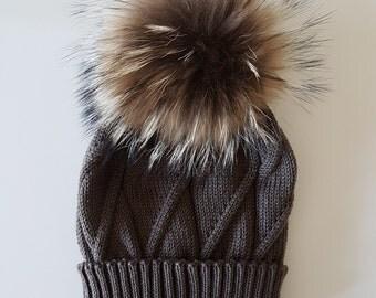 Beanie with oversized real fur Pom pom, soft, elegant beanie accented with a stylish fur pom-pom top and classic diagonal finish