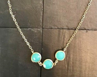 Three chain blue stone necklace.