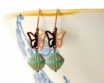 copper earrings with a small butterfly and turquoise bead