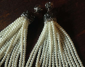 Creamy white pearl tassel earrings with pave caps swing from oxidized silver pave circle post.