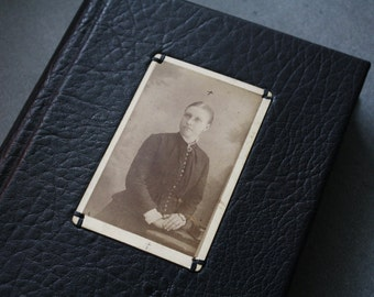 Epitaph - black leatherbound journal with burnt edges. Antique cabinet portrait with crosses on the front cover.