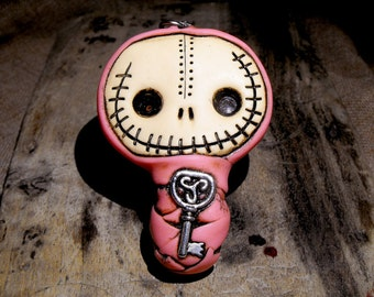 Cute baby mummy keychain in dirty pink. Creepy and cute skull with a celtic key inside his body.